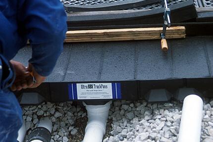 track pan below grade piping